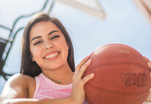 student holding a basketball